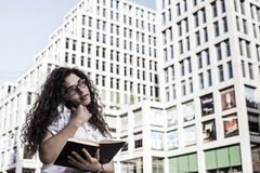 Businnesvrouw die op de mobiele telefoon met cliënt en controles het programma in haar notitieboekje spreekt stock fotografie