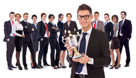 Businss man holding a trophy in fron of his team. Winning business team with a young men executive holding a gold trophy . happy and successful bueinssteam Royalty Free Stock Images