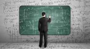 Businssman dessinant la formule mathématique Images stock