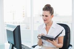 Businsswoman смотря экран компьютера пока держащ еженедельник Стоковое фото RF