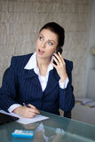 Businsswoman with big eyes get good news by phone. In office Stock Photos