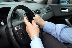 Businwssman genom att använda mobiltelefonen, medan köra bilen Arkivbild