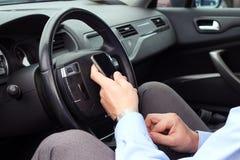 Businwssman unter Verwendung des Handys beim Fahren des Autos Lizenzfreie Stockfotografie