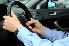 Businwssman using  mobile  phone while driving the car Royalty Free Stock Image