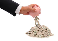 Busisnessman holding piggy bank with bills. Businessmans hand holding a pink piggy bank over a pile of hundred dollar bills with some bills spilling out. Bills Stock Images