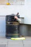 Busker In Bin. Cambridge, England - February 19, 2012: Busker inside a trash bin plays guitar Royalty Free Stock Images
