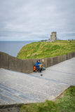 Busker at the Cliffs of Moher. Musician with an accordion sitting on the footpath leading to the O`Briens Tower at the Cliffs of Moher, Ireland Royalty Free Stock Photography