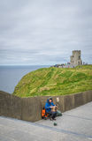 Busker at the Cliffs of Moher. Musician with an accordion sitting on the footpath leading to the O`Briens Tower at the Cliffs of Moher, Ireland Royalty Free Stock Photo