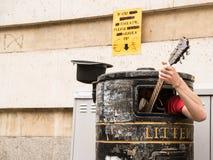 Busker, der Gitarre innerhalb eines Mülleimers singt und spielt Stockbild