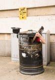 Busker, der Gitarre innerhalb eines Mülleimers singt und spielt Stockfoto