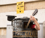 Busker, der Gitarre innerhalb eines Mülleimers singt und spielt Stockbilder