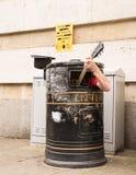 Busker, der Gitarre innerhalb eines Mülleimers singt und spielt Stockfotos