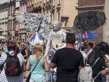 Busker-/gataaktör som kläs som en ängel med enorma vingar, folkmassa som omger honom som väntar för att ta bilder royaltyfria foton
