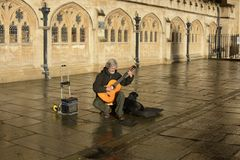 Busker guitarist outside Bath Abbey. England Royalty Free Stock Photography