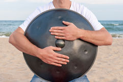 Busker hold the Hang or handpan with sea on Royalty Free Stock Photography