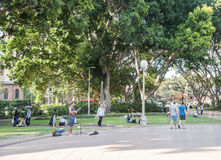 Busker at Hyde Park. SYDNEY,NSW,AUSTRALIA-NOVEMBER 18,2016: People relaxing at Hyde Park with lush fig trees and street musician busker in Sydney, Australia Stock Photos