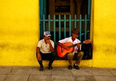 Busker and a man in the streets of Trinidad, Cuba on Christmas Eve 2013. A street musician and another man sitting by the wall of an old yellow building in the Stock Photos