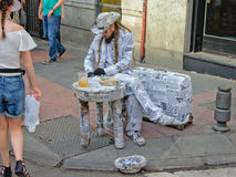 Busker in news paper costume on Madrid flea market. Street performer with a costume made of newspapers, next to a table and suitcase also wrapped in nespaper, on Royalty Free Stock Images
