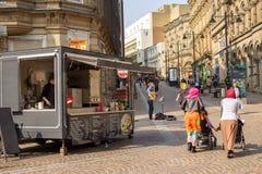 Busker onderhoudt klanten in Bradford, Yorkshire stock foto's