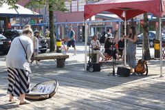 A busker performs at Granville island and a tourist tips while she performs. Granville island in Vancouver has a royalty free stock photography