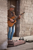 Busker. Perugia, Italy, May 13, 2013. Male musician playing guitar and harmonica busking in a back alley of Perugia Stock Images