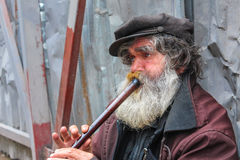 Busker playing flute Stock Image