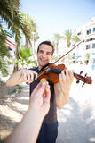 Busker playing violin outside for money. Smiling man playing violin for money outside Stock Image