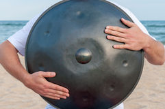 Busker on the sand beach and holding a handpan or hang with sea On Background. The Hang is traditional ethnic drum Royalty Free Stock Photography