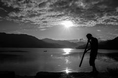 Busker on the shore Phewa lake. The sun sets behind the mountains surrounding the lake. Thick clouds cover the sky to the horizon Royalty Free Stock Images