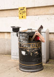 Busker singing and playing guitar inside a rubbish bin. On a street Stock Photo