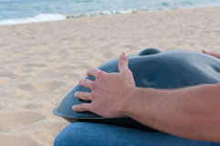 Busker sit on sand and play the Hang or handpan Stock Image