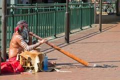 Busker sitting and blowing didgeridoo, Australian Aboriginal win. SYDNEY, AUSTRALIA - APRIL, 2016 : Busker sitting and blowing didgeridoo, Australian Aboriginal Stock Photo