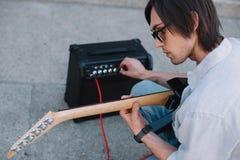 Busker som justerar gitarrförstärkaren, medan utföra på soligt fotografering för bildbyråer
