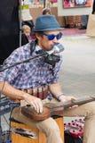 Busker som sjunger och spelar gitarrmusik i Eumundi, Queensland, Australien royaltyfri bild