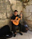 Busker som spelar den klassiska gitarren vid den historiska porten arkivbilder