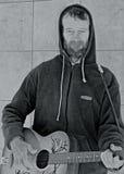 Busker som spelar hans gitarr arkivfoton