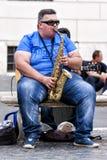 Busker som spelar saxofonen som placeras på en bänk fotografering för bildbyråer