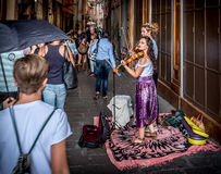 Busker violinist. Bologna, Italy, 18 September 2016: two buskers violinists perform for the passersby in the historic district of Bologna Stock Image