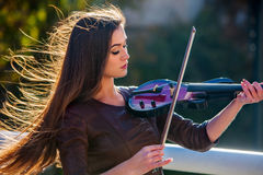 Busker woman perform music on violin park outdoor. Girl performing . Royalty Free Stock Images