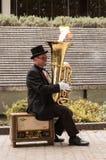 Buskermusiker, der eine Tuba mit den Flammen herauskommen von ihr spielt Stockbilder