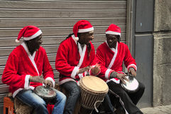 Buskers,high spirits,christmas,happiness,african,men,street artists. Naples. Toledo street on saturday. Buskers with clothing christmas. Christmas time Royalty Free Stock Photo