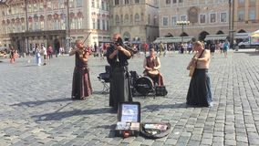 Buskers in  Old Town Hall - Prague. PRAGUE - AUGUST 4: Street performers in costume play Celtic in  Old Town Square - Old Town Hall or Clock's square on august 4 stock footage