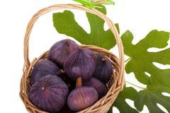 Busket van verse fig. met bladeren op wit Stock Afbeelding