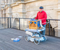 Busking in Arles, France. ARLES, FRANCE - APRIL 12 : Busking man play large music box on vendor near Amphitheater in Arles, France, on April 12, 2017 stock photo