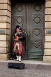 Busking bagpiper on the street in Edinburgh. EDINBURGH, UK - DECEMBER 09 2017: The busking man plays bagpipe on the street on December 09,2017 in Edinburgh, UK royalty free stock photography