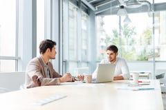 2 busnessmen при компьтер-книжка сидя и говоря в офисе Стоковое Фото