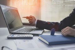 Busniess man finance market analyst working at office at white table.Businessman analyze document and the calculator in hands.Grap. Hs and diagram Royalty Free Stock Photo