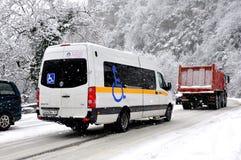 Buss för rullstolen som kör i en snowstorm Arkivbild