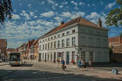 Buss, folk och byggnad i en hörngata av Bruges Arkivbild