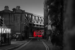 Buss London för dubbel däckare under bron arkivbilder